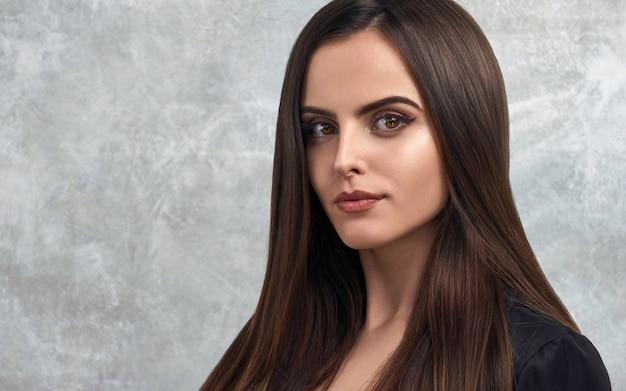 Chica morena con cabello sano perfecto y piel con maquillaje natural con espacio de copia