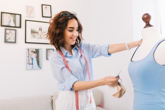 Una chica morena con una camisa azul está trabajando en el estudio del taller. está seleccionando un material para el vestido azul.