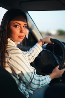 Chica morena con una camisa a rayas y jeans conduciendo un coche