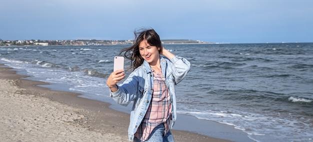 Chica morena con una chaqueta de mezclilla hace una foto en un teléfono con cámara selfie contra el mar.