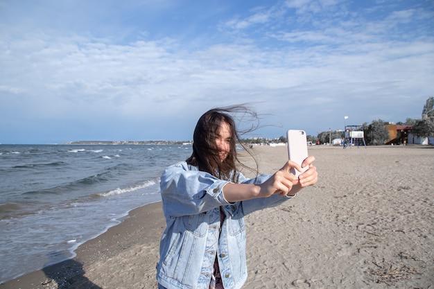 Chica morena con una chaqueta de mezclilla toma una foto en un teléfono con cámara selfie contra la pared del mar. el concepto de viaje y nuevas experiencias.