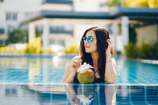 Chica morena comiendo fruta junto a la piscina