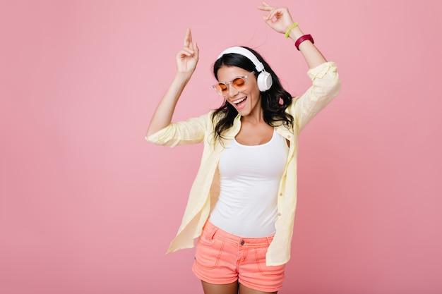 Chica morena delgada inspirada en gafas de sol divertidas bailando y agitando las manos. riendo a mujer joven de pelo oscuro con camisa amarilla disfrutando de la música en auriculares con los ojos cerrados.