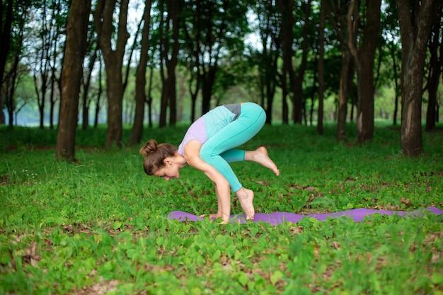 Chica morena delgada practica deportes y realiza posturas de yoga hermosas y sofisticadas en un parque de verano