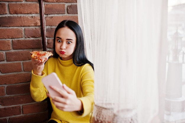 Chica morena divertida en suéter amarillo comiendo pizza en el restaurante y haciendo selfie.
