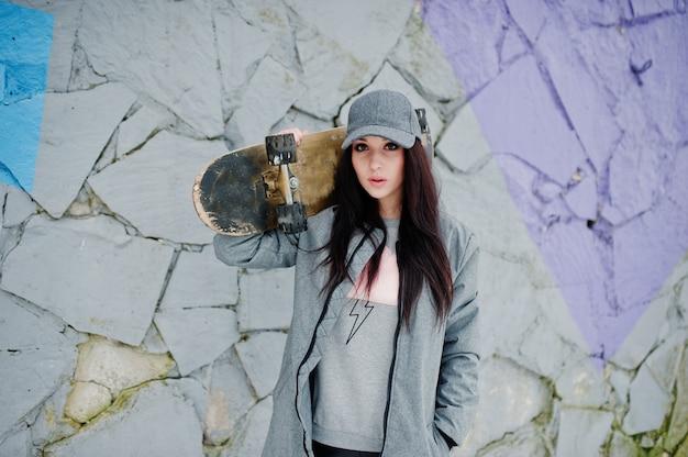 Chica morena elegante en patineta gris con patín
