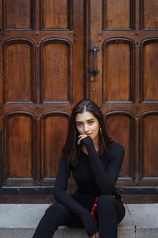 Chica morena elegante sentado en las escaleras