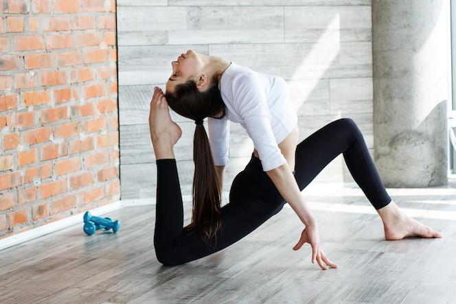 Chica morena en ropa deportiva blanco y negro hace yoga y estiramientos en el gimnasio