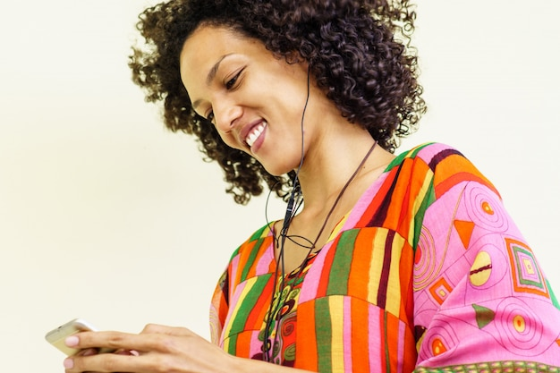 Chica morena escuchando música con su teléfono celular