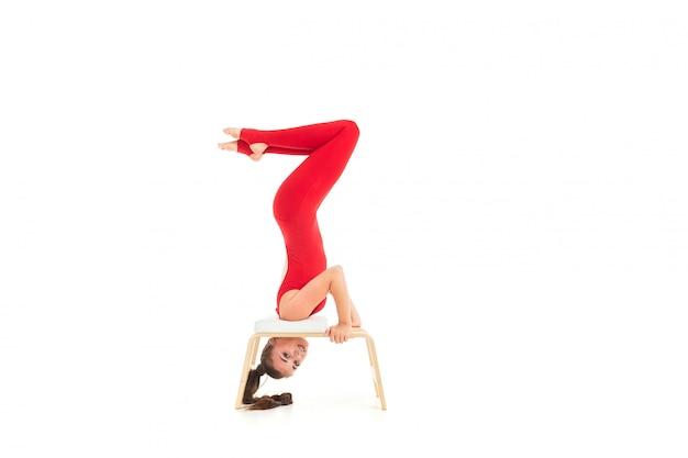 Chica morena europea en un chándal rojo desea ejercicios gimnásticos boca abajo sobre blanco