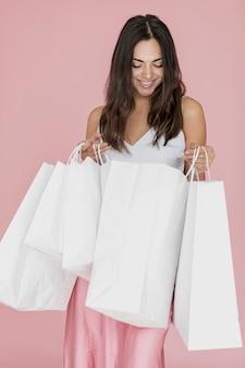 Chica morena con falda rosa y muchas redes de compras