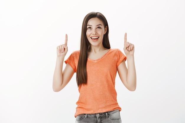 Chica morena feliz soñadora apuntando con el dedo hacia arriba, mirando fascinado y sonriendo ampliamente