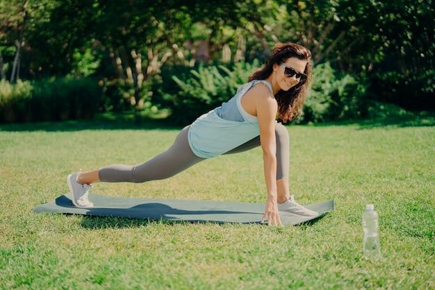Chica morena flexible en ropa deportiva hace ejercicios en la colchoneta de fitness