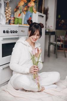 Chica morena con flores rosas.