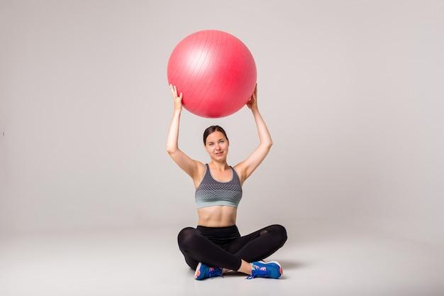 Chica morena haciendo deporte con una pelota de fitness en un blanco