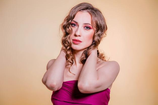 Chica morena hermosa sensual con maquillaje rojo, pelo rizado y un top burdeos posando sobre fondo de color limón. foto vertical