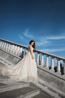 Chica morena hermosa, sexy y de moda en vestido de novia de encaje blanco posando en las escaleras con cielo azul de verano en el fondo