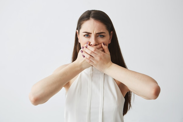 Chica morena joven disgustada que cubre la boca con la mano sobre fondo blanco.