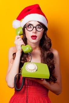 Chica morena joven en vestido rojo y sombrero de santa claus y arco con teléfono fijo verde sosteniendo el auricular en púrpura
