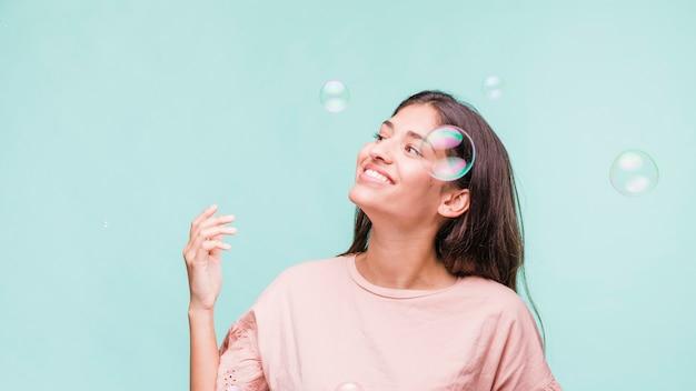Chica morena jugando con burbujas de jabón