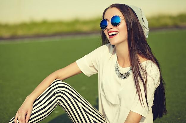 Chica morena de moda posando al aire libre