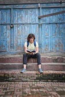Chica morena occidental con mochila sentada en los escalones de piedra marrón mirando hacia adelante en la calle leyendo una guía de viaje con una hermosa puerta de madera con rayas azules. foto vertical