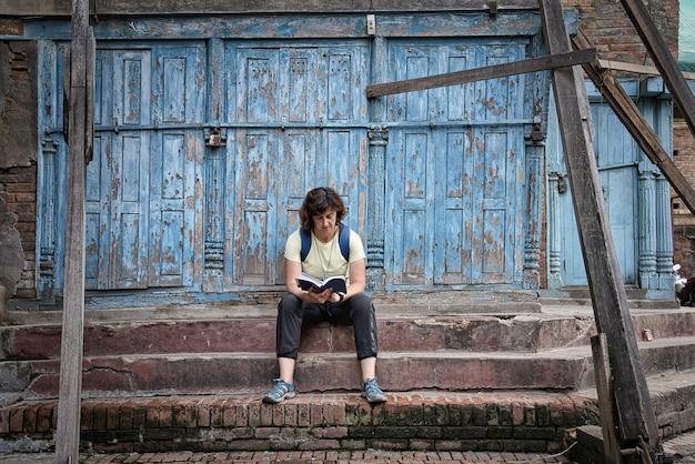 Chica morena occidental con mochila sentado en los escalones de piedra marrón en la calle leyendo una guía de viaje con una hermosa puerta de madera pelada azul.
