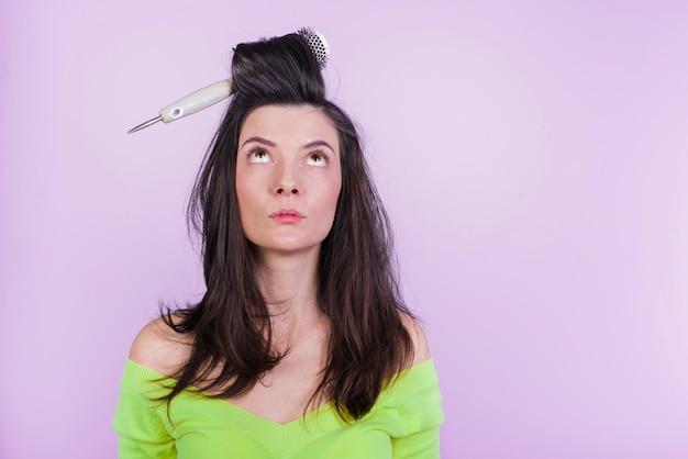 Chica morena posando con cepillo