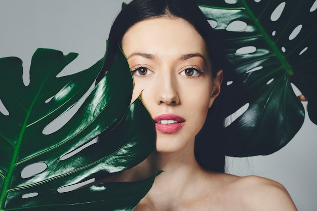 Chica morena posando con hojas exóticas