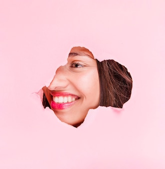 Chica morena posando a través de agujero de papel