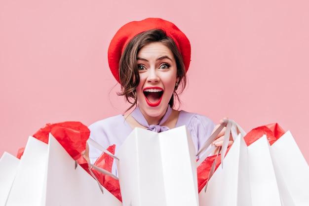 Chica morena rizada contenta con sombrero rojo mira felizmente a cámara y tiene paquetes.