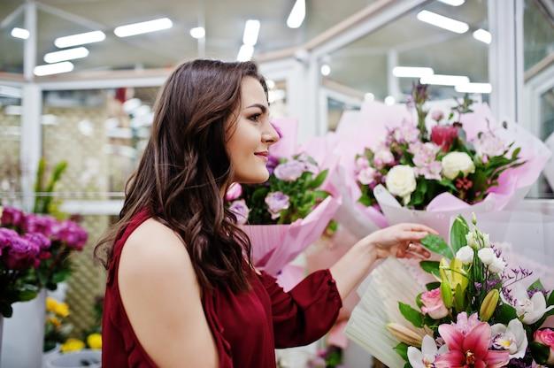 Chica morena en rojo comprar flores en la tienda de flores.