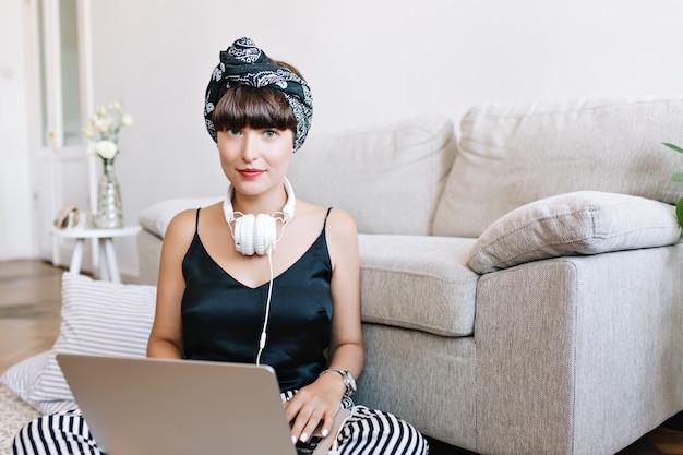 Chica morena romántica con ojos azules posando por qué usar una computadora portátil enfriándose en el piso frente al sofá