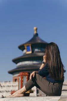 Chica morena sentada en los escalones por el templo de heven en china