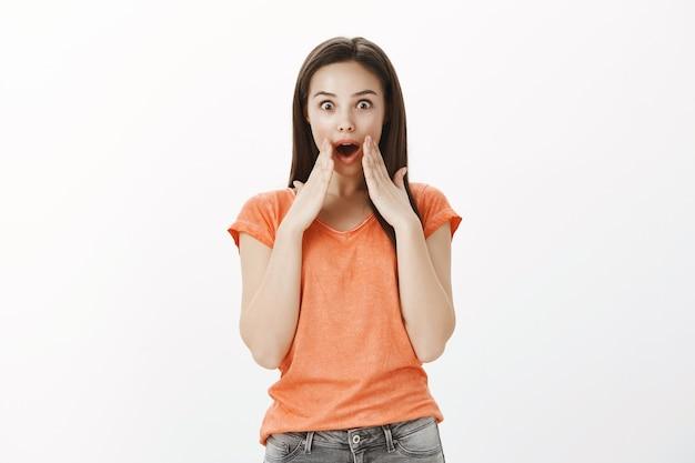 Chica morena sorprendida e impresionada jadeando asombrada, cubrirse la boca con las manos asombradas, diciendo wow