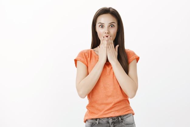 Chica morena sorprendida e impresionada jadeando asombrada, cubrirse la boca con las manos asombradas