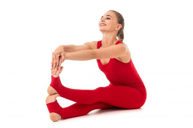 Chica morena en un traje deportivo rojo realiza ejercicios gimnásticos en blanco
