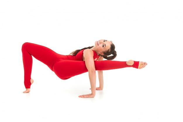 Chica morena en un traje deportivo rojo realiza ejercicios gimnásticos para flexibilidad en blanco