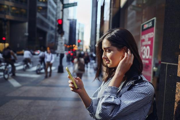 Chica morena usando su celular para llegar a un amigo