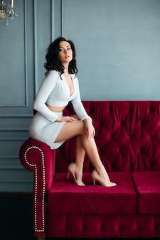 Chica morena con vestido azul y tacones altos sentado en el sofá de borgoña.