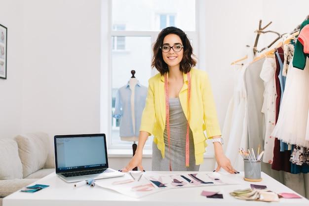 Una chica morena con un vestido gris y una chaqueta amarilla está de pie cerca de la mesa en un taller. tiene muchas cosas creativas sobre la mesa. ella sonríe a la cámara.
