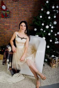 Chica morena en vestido presentado cerca de árbol de año nuevo con decoración de navidad en la sala de estudio de ladrillo.