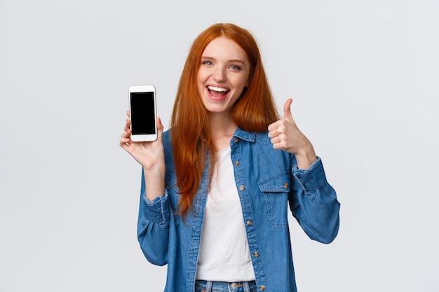 Chica mostrando amigo fresco nuevo juego móvil. atractiva mujer pelirroja alegre que sostiene el teléfono inteligente, presenta la aplicación, la aplicación del teléfono, levanta el pulgar y sonríe con aprobación, recomendando