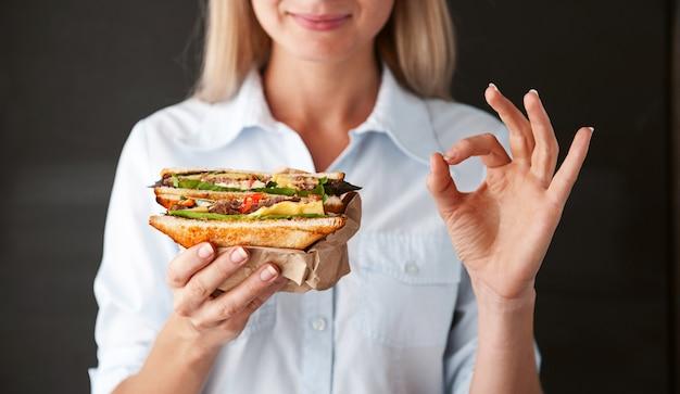 Chica mostrando bien sosteniendo un sandwich