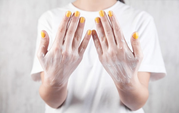 Chica mostrando crema en las manos. piel suave