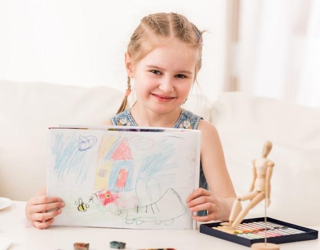 Chica mostrando dibujo en colores pastel