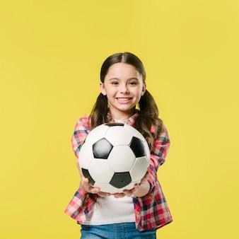Chica mostrando fútbol en estudio