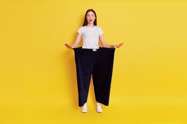 Chica mostrando pérdida de peso, chica asombrada con la boca abierta, dama de camiseta blanca con pantalones negros viejos de gran tamaño, de pie aislado sobre una pared amarilla.