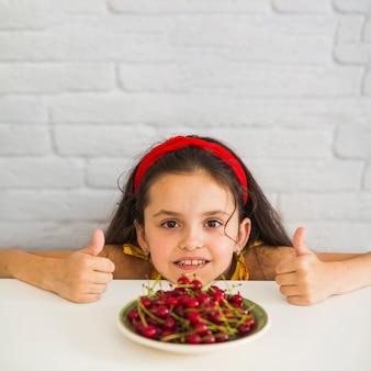 Chica mostrando pulgar arriba signo en frente de cerezas rojas en placa sobre el escritorio