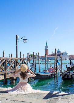 Chica en el muelle con góndolas en venecia